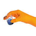 orange gloved hand holding a beaker with a blue chemical
